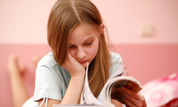 Girl reading book reluctantly